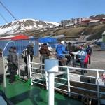 Turister går i land i Barentsburg. Trappene opp til byen i bakgrunnen